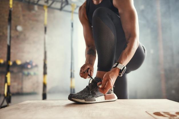 彼女の靴ひもを結ぶスポーツ服を着た美しい若い女性のトレーニングのトリミングされた写真の準備