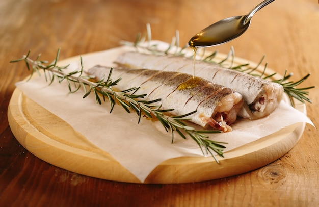 Preparing fresh hake fish with salt, rosemary staws and olive oil.