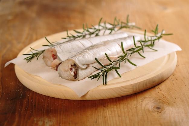 Preparing fresh hake fish with salt and rosemary staws.