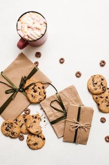 お菓子とラテのカップでギフトを準備しています。自家製チョコレートスコーンとマシュマロとおいしいホットドリンク、上面図の写真と白いテーブルの上の小さなエレガントなプレゼント