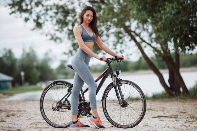 Prepararsi per andare alla prossima destinazione. ciclista femminile con una buona forma del corpo in piedi con la sua bici sulla spiaggia durante il giorno