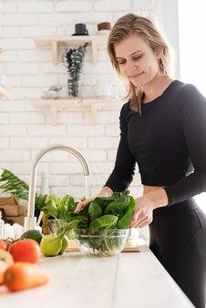 健康食品の準備。キッチンでほうれん草を洗うスポーツ服の女性