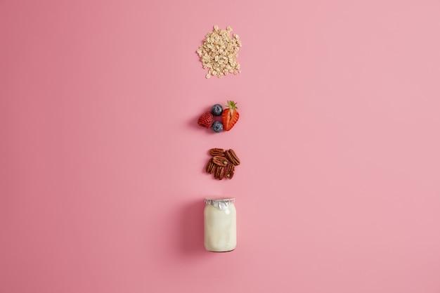 健康的なオートミールのお粥を食べる準備をしています。天然ヨーグルト、ホールナッツ、熟したブルーベリー、イチゴ、オーツ麦の瓶を混ぜ合わせます。新鮮なオーガニックスナック。健康とダイエットの概念。朝食のアイデア
