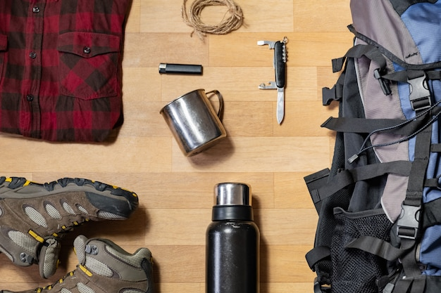 Preparing for a hiking trip: backpacking things and clothes flat lay. top view of trekking boots, tourist rucksack and camping acessories on the floor