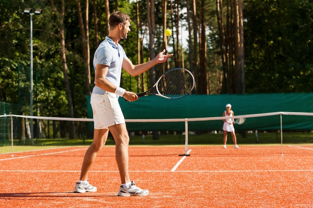 Preparing to his best serve. full length of man and woman playing tennis on tennis court