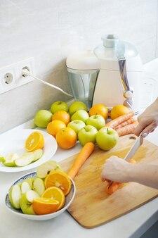 사과, 오렌지, 당근으로 만든 신선한 수제 주스를 준비합니다.