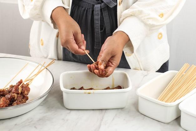 Приготовление домашнего сатая из баранины (сатэ камбинг) для меню идул адха. сейт камбинг - популярная уличная еда в индонезии. концепция чистой кухни