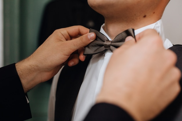 Preparing for the important event, putting on bow tie, front view