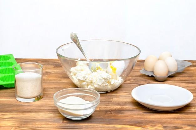 코티지 치즈 바나나 머핀 컵케이크 캐서롤을 가정 주방 요리, 온라인 요리, 조리법 지침에서 만들기 위해 큰 그릇에 재료를 준비합니다.