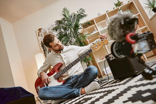 Готовит инструмент красивый музыкальный блогер мужского пола настраивает электрогитару для записи нового видео