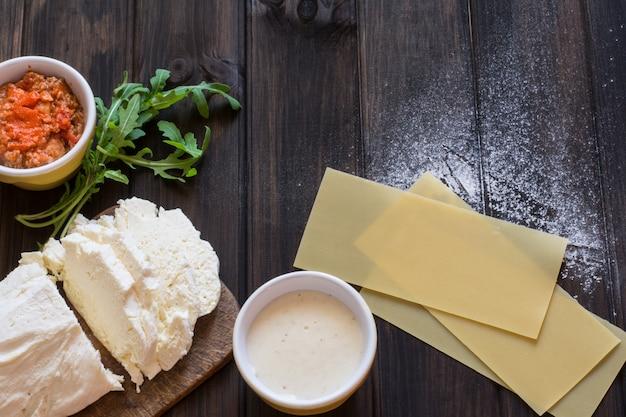 Preparing lasagna. raw lasagna dough, mozarella cheese, bolognese sauce, bechamel sauce, a