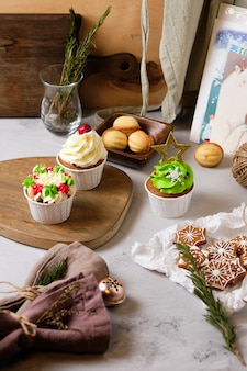 Preparing a new year's gift for friends. sweets for christmas. new year's gingerbread cookies and cupcakes with cream cheese cream and caramel filling.