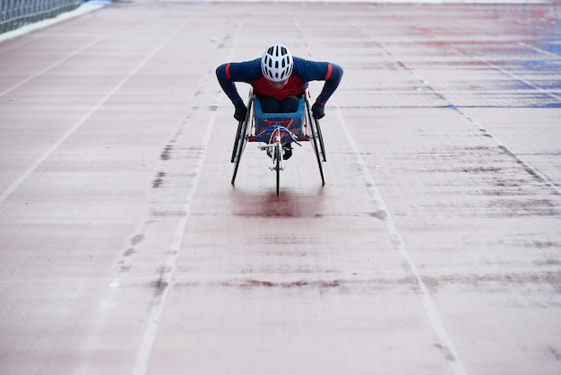 Preparing for paralympics. determined wheelchair racer in sportswear and helmet reaching finish line while training at outdoor track and field stadium