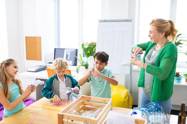 Готовим пластиковые бутылки. молодой приятный учитель и дети готовят пластиковые бутылки для будущей переработки