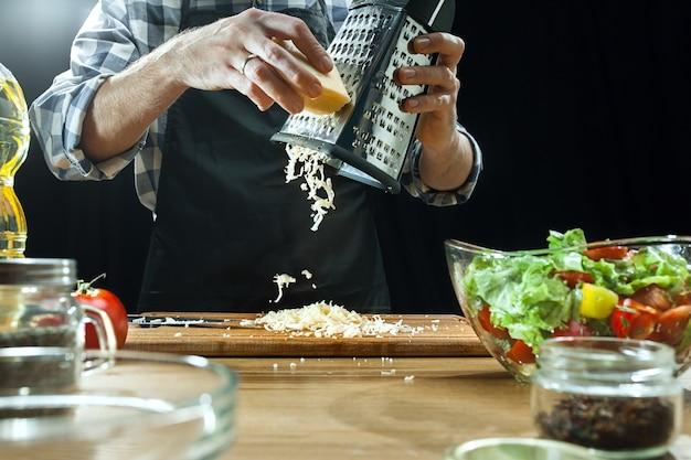 サラダを準備しています。新鮮な野菜を切る女性シェフ。調理プロセス。セレクティブフォーカス。健康食品、キッチン、サラダ、ダイエット、料理の有機コンセプト