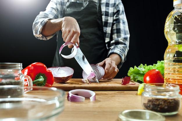 Готовим салат. женский шеф-повар резки свежих овощей. процесс приготовления. выборочный фокус