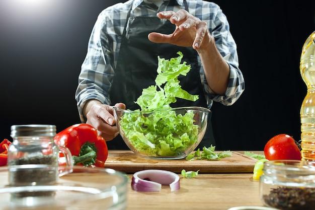 サラダを準備しています。女性シェフが新鮮な野菜をカットします。