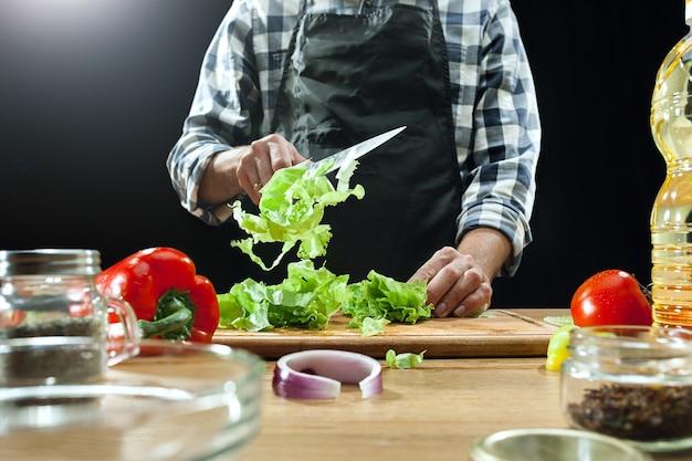 サラダを準備しています。新鮮な野菜を切る女性シェフ。