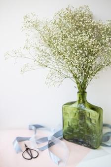 Готовя букет к свадебной церемонии, букет из белых цветов гипсофилы стоит в зеленой вазе вместе с лентами и ножницами.