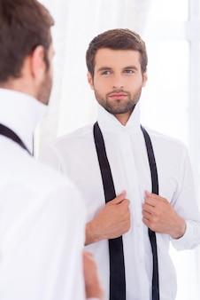 Подготовка к особому дню. красивый молодой человек в белой рубашке и развязанном галстуке стоит у зеркала