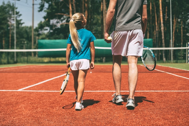 ビッグゲームの準備。テニスラケットを運び、テニスコートで彼女の近くを歩いている父親を見ているスポーツウェアの小さなブロンドの髪の少女の背面図
