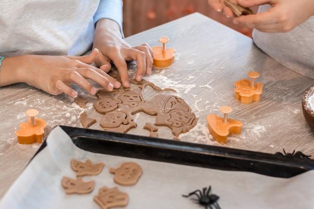 Подготовка к празднованию хэллоуина и приготовление угощения. дети вырезали формы для печенья на хэллоуин и противень сырого печенья на столе. образ жизни
