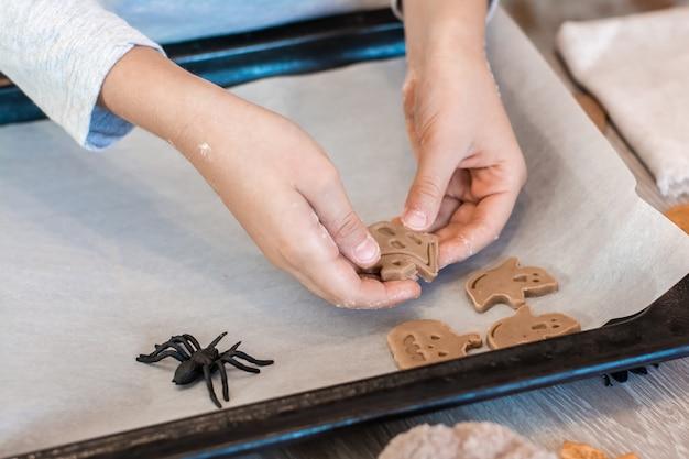 Подготовка к празднованию хэллоуина и приготовление угощения. детские руки раскладывают сырое печенье на хэллоуин на противне. образ жизни