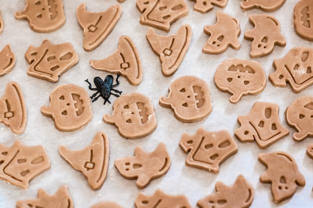 Подготовка к празднованию хэллоуина и приготовление угощения. сырые готовые к выпечке печенье на хэллоуин на бумаге на противне. образ жизни