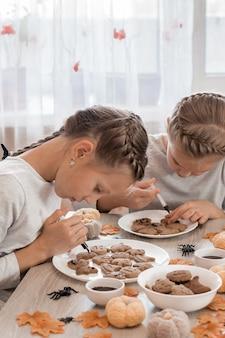 Подготовка к празднованию хэллоуина и приготовление угощения. две девушки украшают имбирные пряники на тарелки шоколадной глазурью. образ жизни