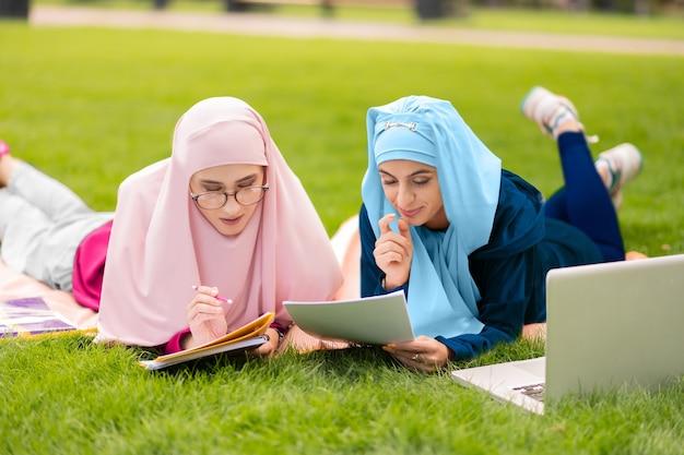試験の準備。草の上に座って一緒に試験の準備をしている2人の賢いイスラム教徒の学生