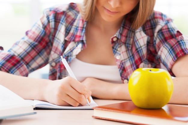 Подготовка к экзаменам. обрезанное изображение уверенной в себе девочки-подростка, обучающейся, сидя за столом