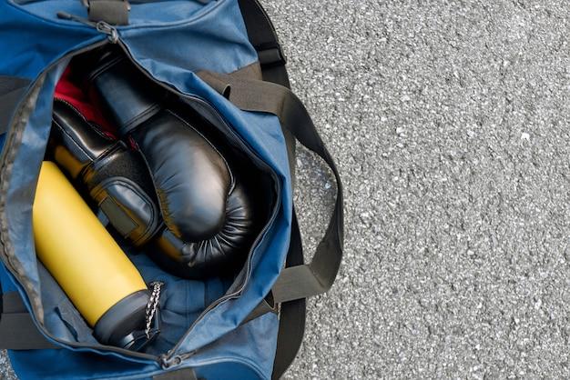 싸울 준비를 합니다. 아스팔트 배경에 물이 있는 스포츠 가방과 권투 장갑의 클로즈업