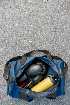 싸울 준비를 합니다. 아스팔트 배경에 물이 있는 스포츠 가방과 권투 장갑의 상위 뷰