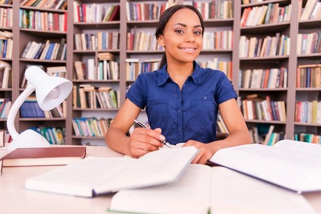 彼女の最終試験の準備。カメラを見て、図書館の机に座って笑っている自信を持って若い黒人女性