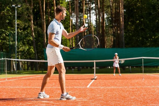 최고의 서브를 준비하고 있습니다. 테니스 코트에서 테니스를 치는 남녀의 전체 길이