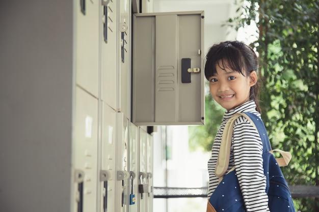 수업 준비 중입니다. 수업 전에 탈의실에 있는 사물함에 가방을 넣고 있는 어린 여학생.
