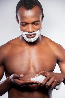 Подготовка к бритью. красивый молодой африканский мужчина наносит крем для бритья на лицо, стоя на сером фоне
