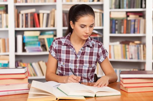 시험 준비. 도서관 책상에 앉아 있는 동안 메모장에 무언가를 쓰고 책을 읽는 사려 깊은 젊은 여성