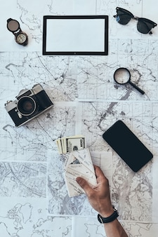 旅行の準備をしています。スマートフォンでパスポートとお金を保持している男の上面図を閉じる