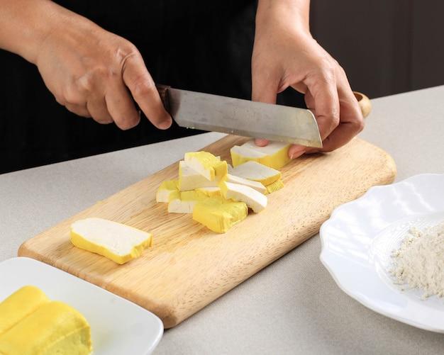비건 식사 준비. 나무 판자에 칼로 노란 두부를 절단 하는 여성 아시아 요리사의 손