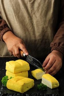 비건 식사 준비. 여성 아시아 셰프의 손으로 노란색 두부를 검은 도마에 칼로 큐브로 자르고 건강한 요리를 위한 개념