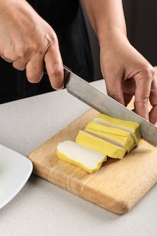 비건 식사 준비. 여성 아시아 요리사의 손으로 나무 판자에 칼로 노란 두부를 절단