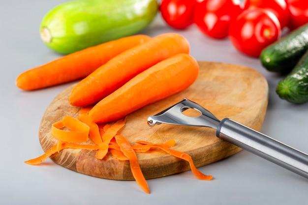 야채 준비. 야채와 함께 나무 식탁에 당근 껍질.