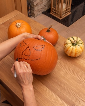 Preperations for halloween ,woomanns hands making sketch on pumpkin .