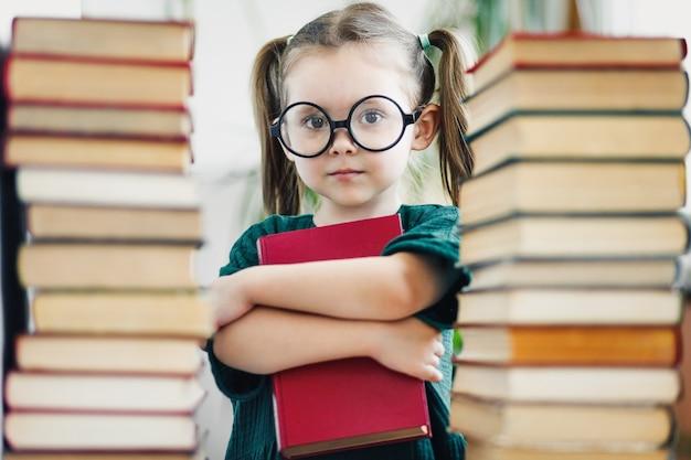 Девушка дошкольного возраста в больших круглых очках, держа красную книгу среди стопок книг.