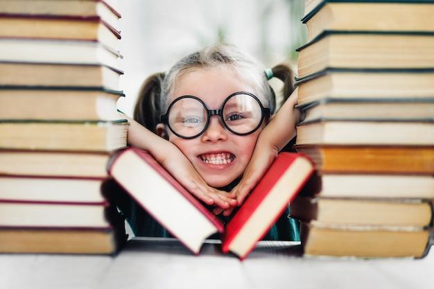 Девочка дошкольного возраста с удивленным лицом в больших забавных очках среди стопки книг.