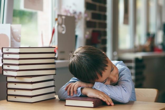 유치원 소년 옆으로 책의 스택과 함께 테이블에 자입니다. 피곤한 소년은 공부하는 동안 도서관에서 잠들었습니다.