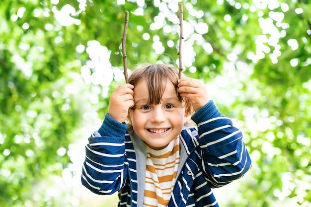 就学前の男の子は木の棒で夏の森で遊んでいます。屋外の公園で剥き出しのジャケットを着ているsmilyng面白い幼児の少年の肖像画。子供との週末。