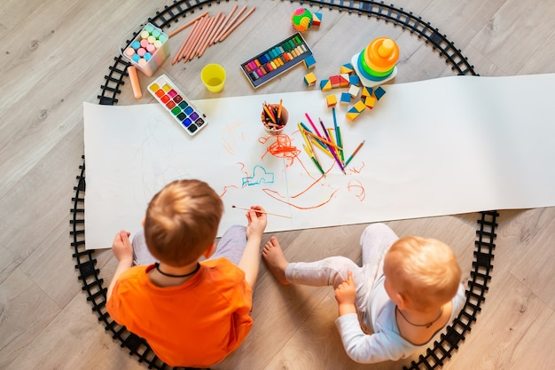 Preschool boys drawing on floor on paper, playing with educational toys - blocks, train, railroad, vehicles at home or daycare. toys for preschool and kindergarten. top view
