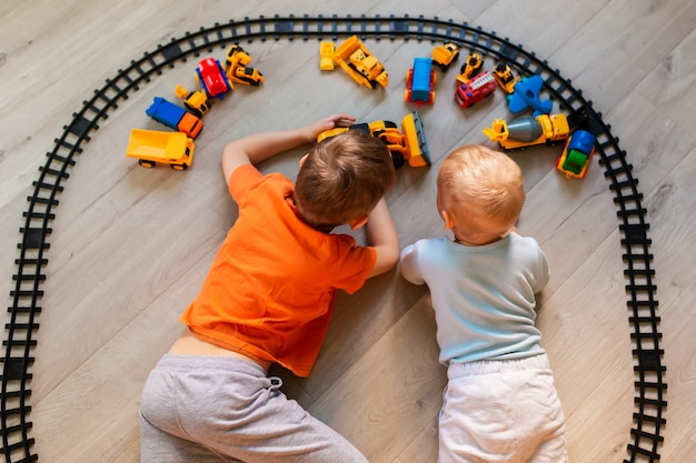 Preschool boys drawing on floor on paper, playing with educational toys - blocks, train, railroad, vehicles at home or daycare. toys for preschool and kindergarten. top view.